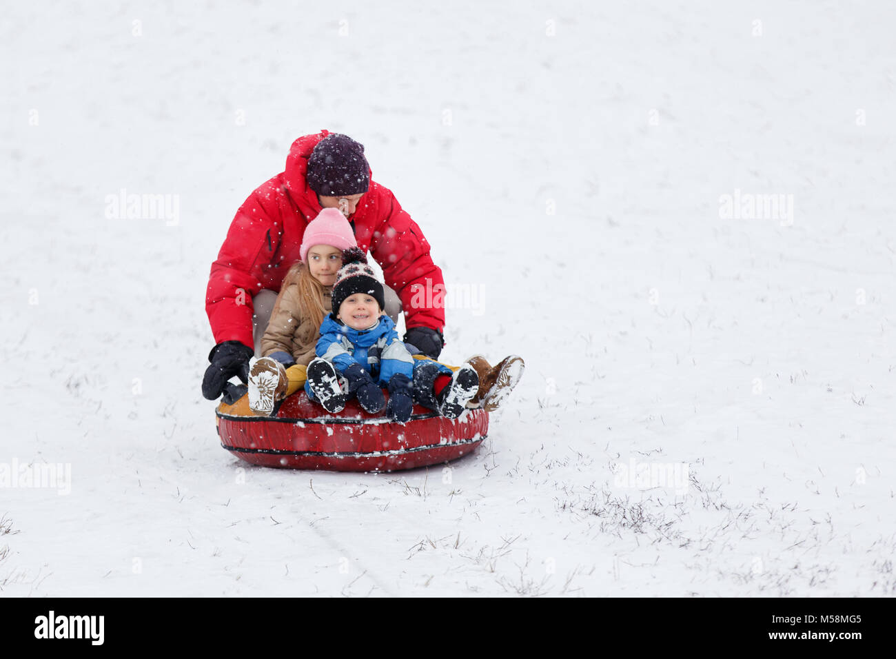 Photo of happy father, daughter and son on tubing in winter park - Stock Image
