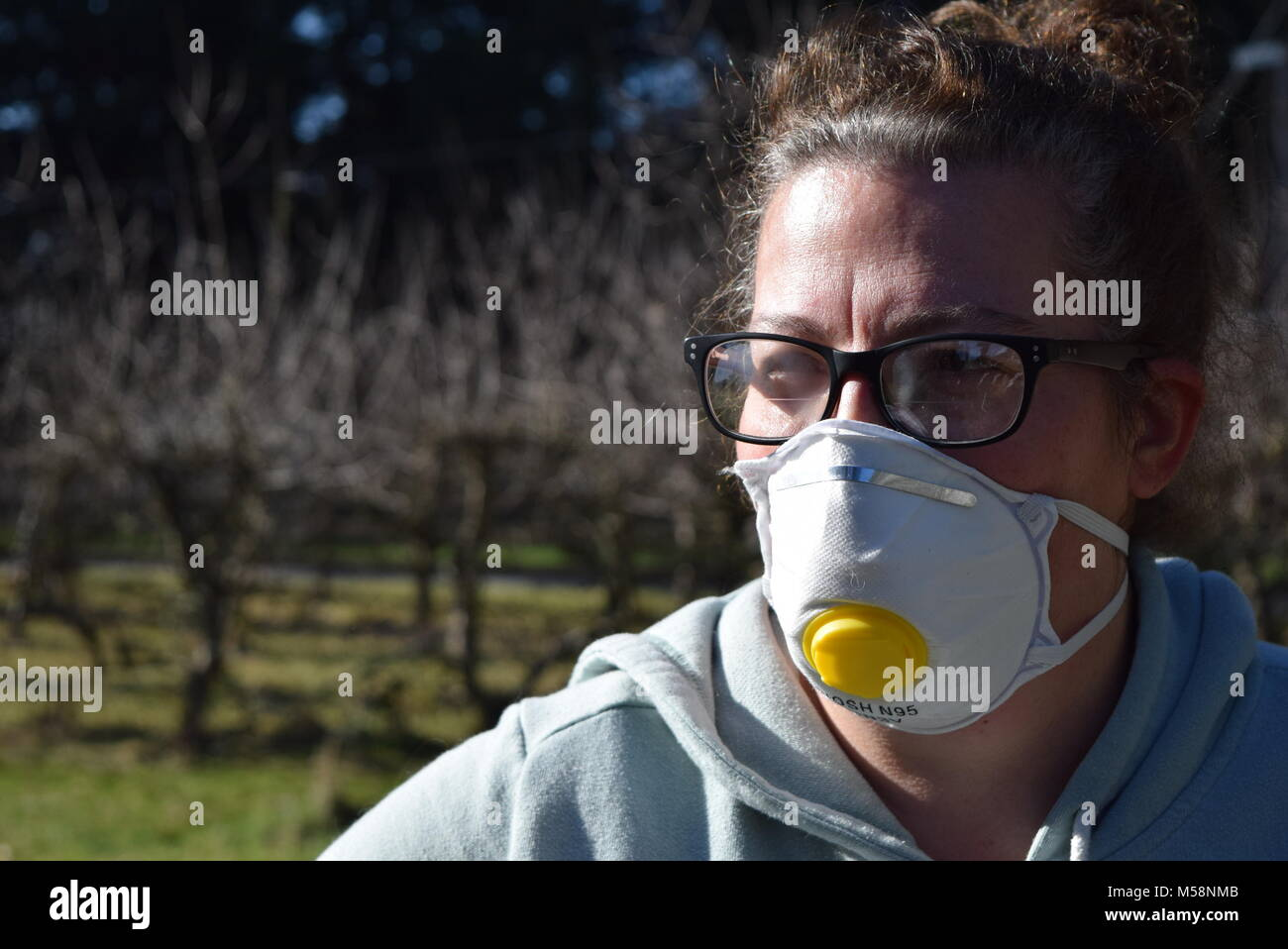Woman wearing a dust mask as she stares into the souls of her enemies before she crushes them in the palms of her - Stock Image
