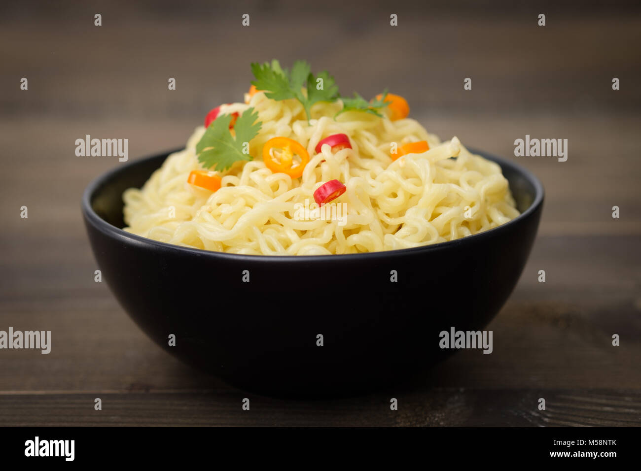 Still life instant noodles with pepper on wooden table, junk food or fast food concept. - Stock Image