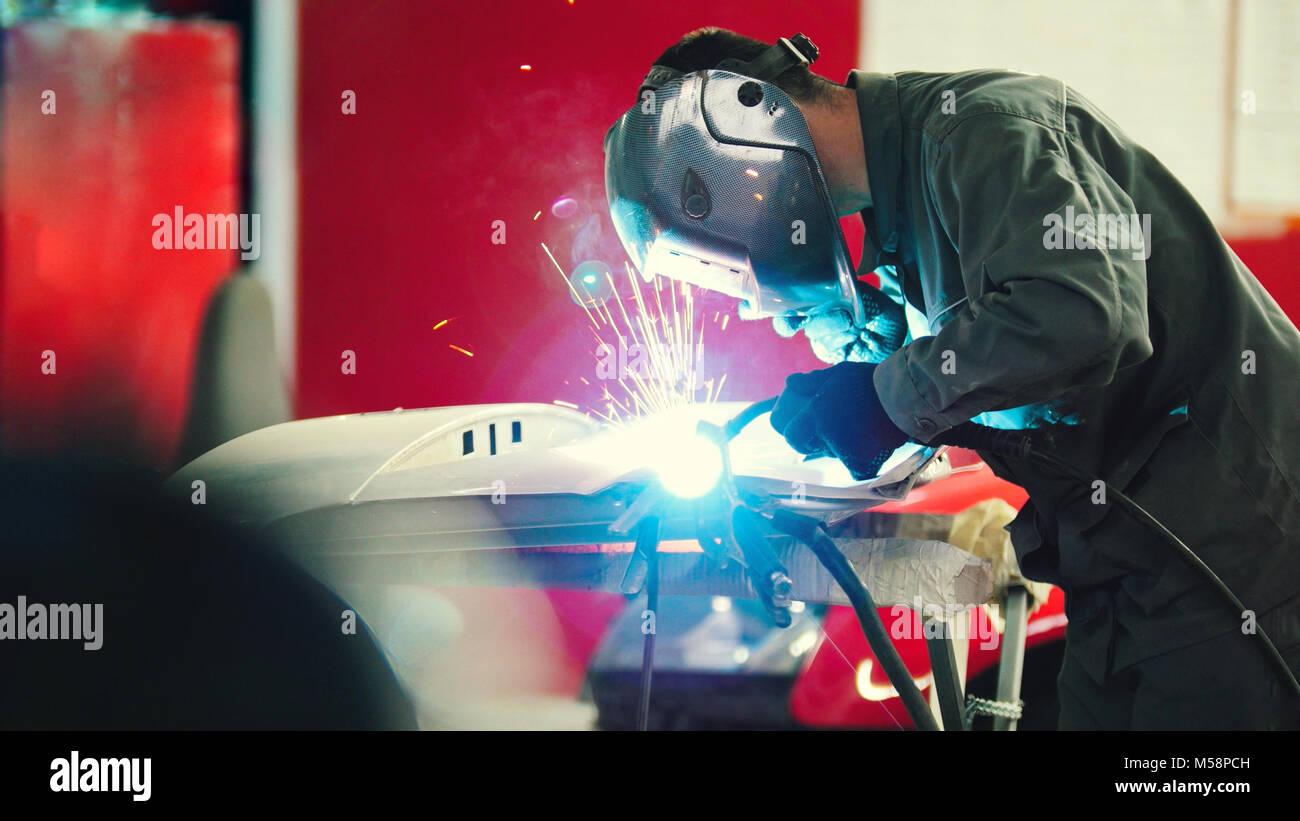 Welding industrial: worker in helmet repair detail in car auto service - blue sparklers - Stock Image