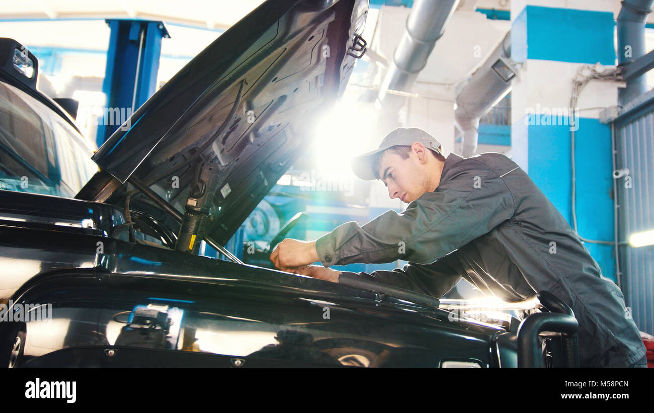 Mechanic in car service - repairing in engine compartment for luxury SUV - Stock Image