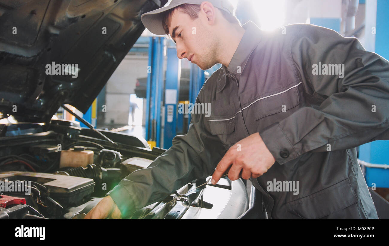 Mechanic in overalls checks level of engine oil in the car - automobile service repairing - Stock Image