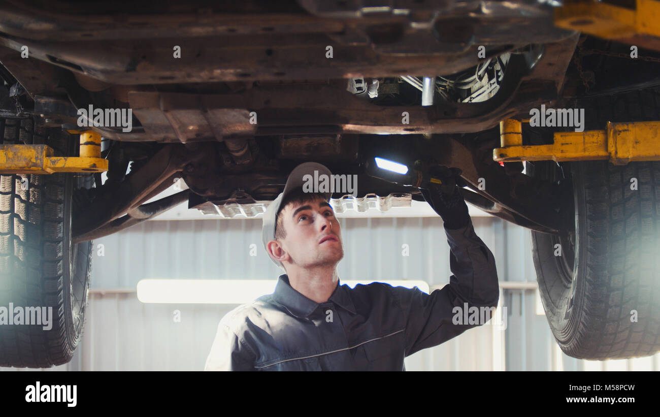 Car service - a mechanic checks the suspension of SUV - Stock Image