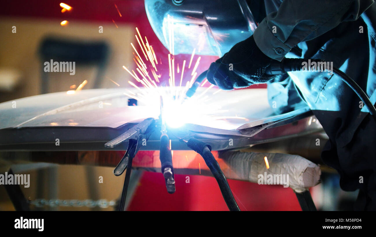 Welding industrial: worker in helmet repair detail in car service - Stock Image