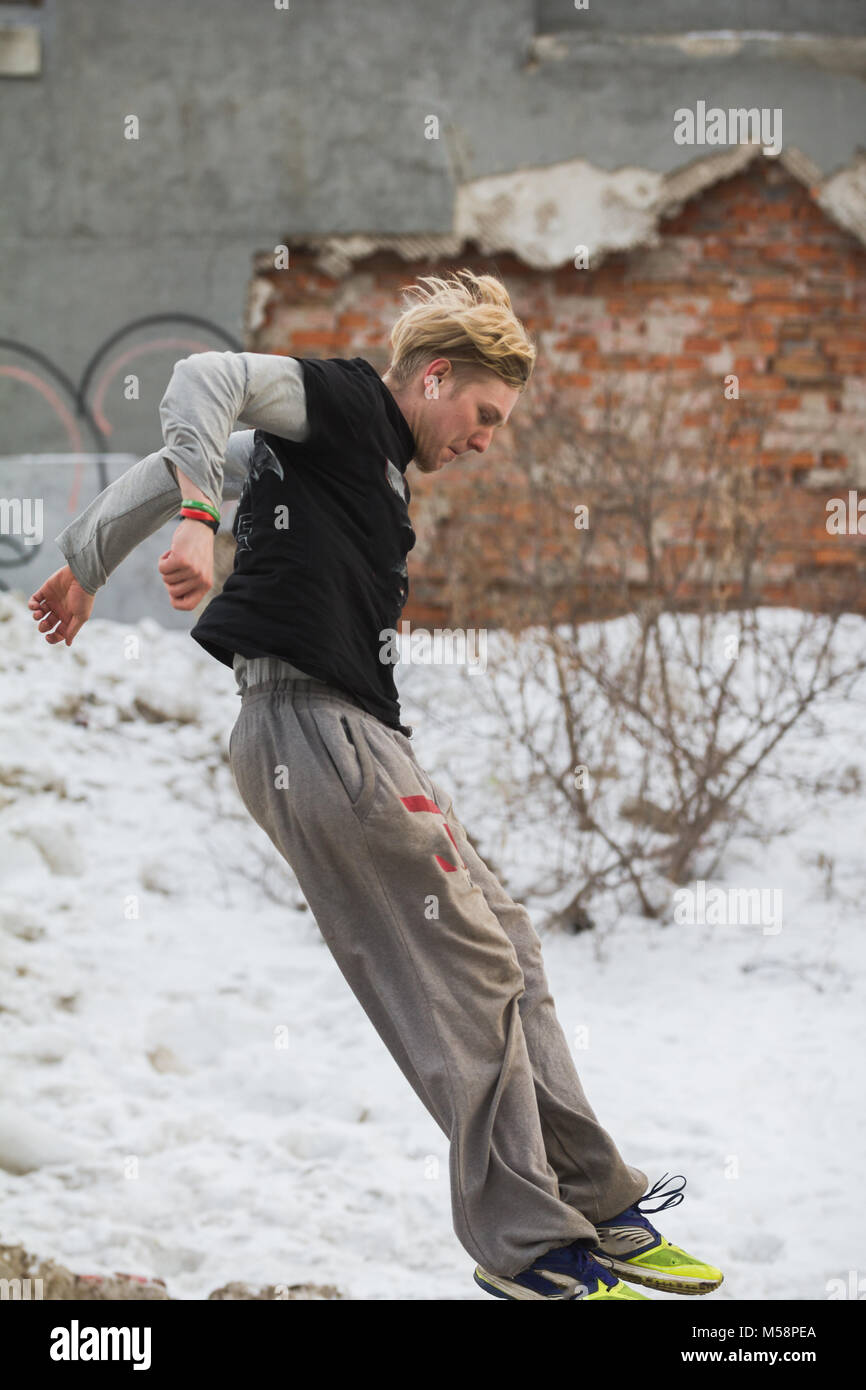 Parkour jumping in winter snow park - free-run training - Stock Image
