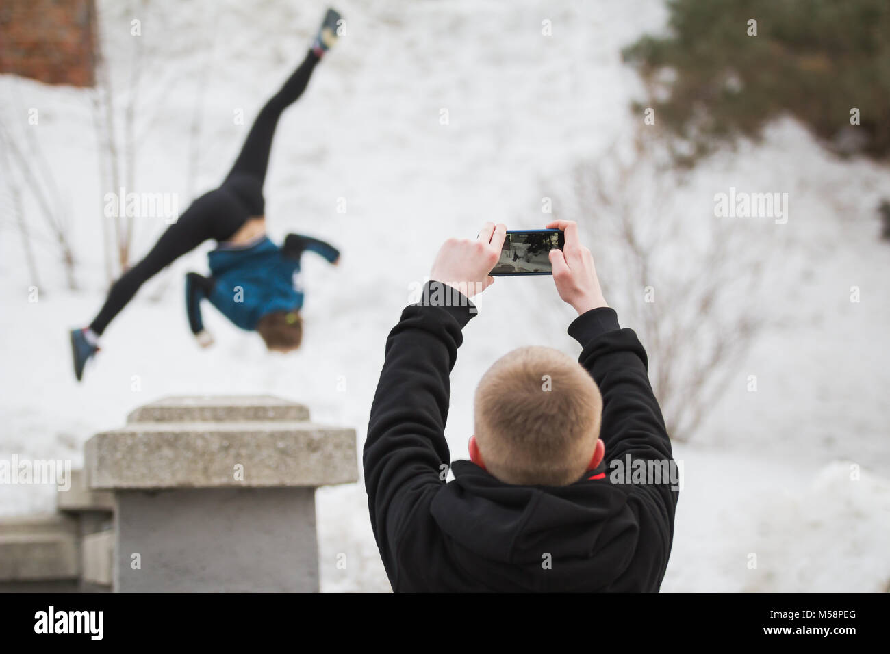 Teenager makes photo on smartphone of acrobatic jump girl in winter city park - parkour concept - Stock Image