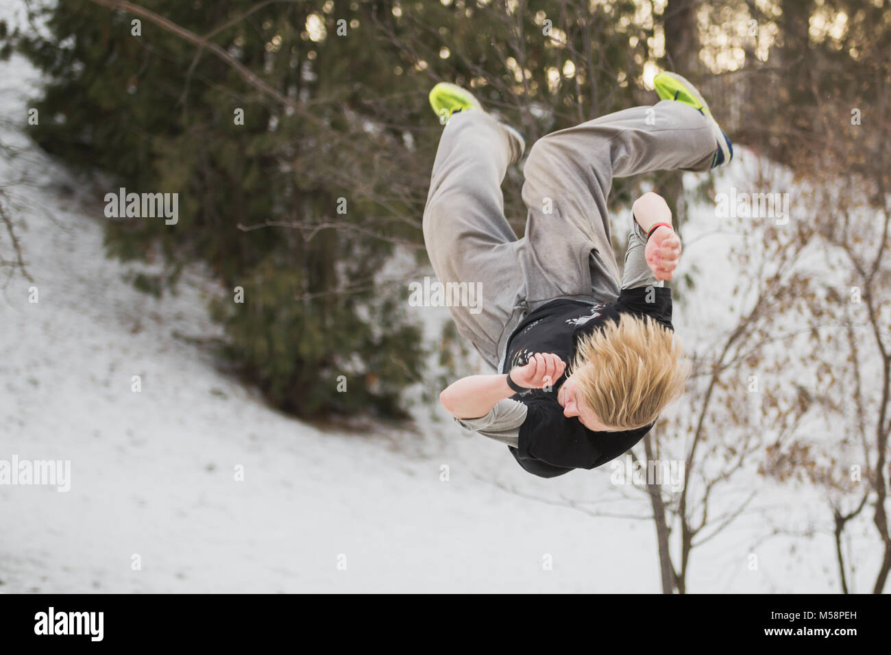 Backflip parkour jumping in winter snow park - free-run training - Stock Image