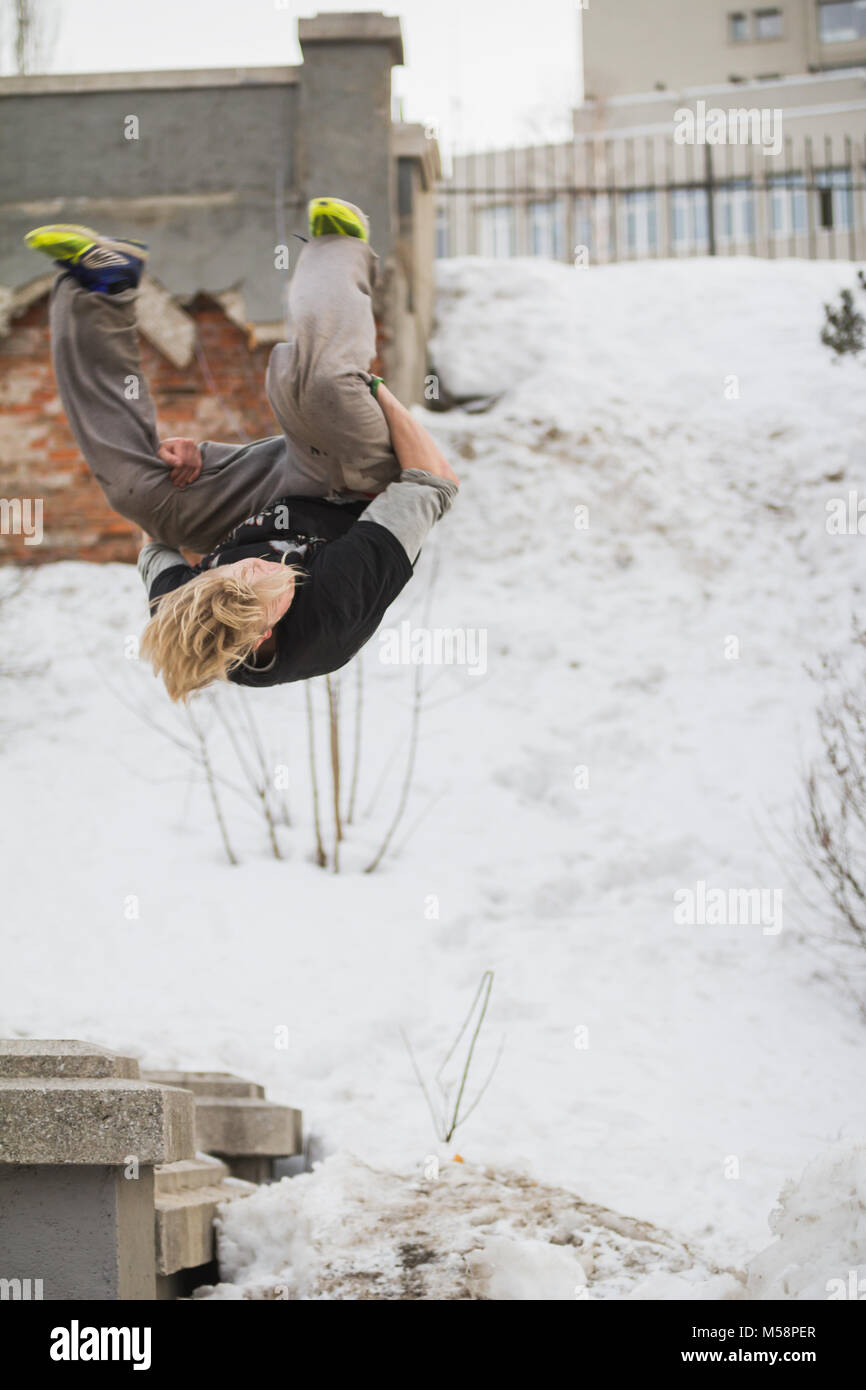 Teenager blonde hair guy training parkour jump flip in the snow covered park - Stock Image