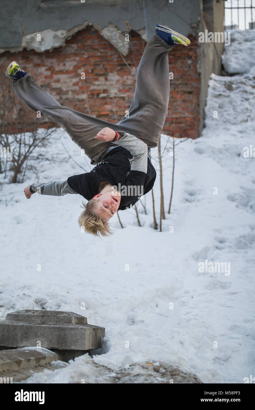 Backflip parkour in winter snow park - blonde hair teenager - Stock Image