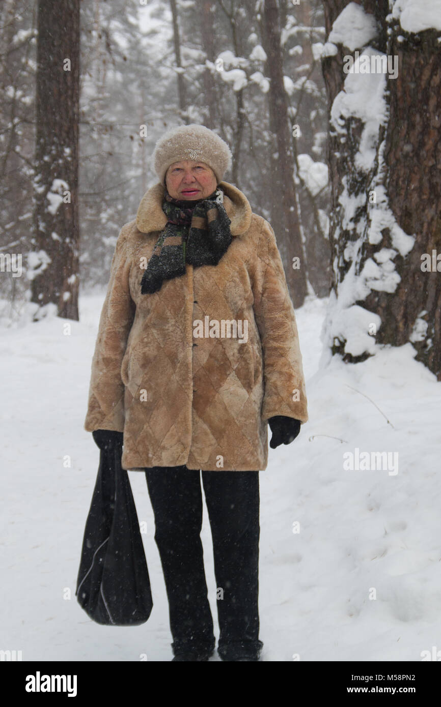 ba6161f53 Portrait of old lady fur coat and hat standing in cold winter snow covered  forest