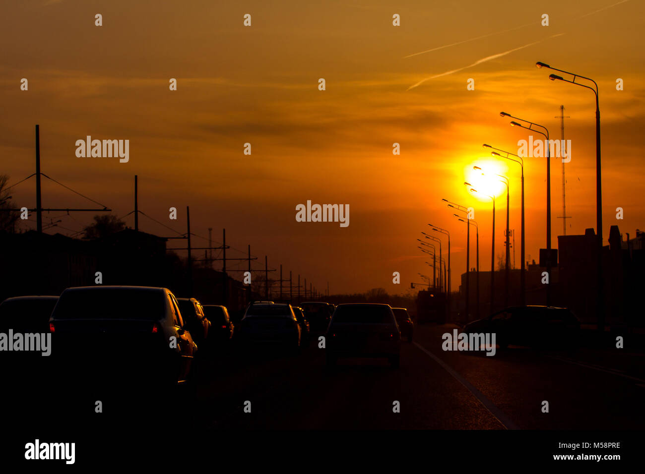 Car traffic against the sunset background - modern city - silhouette - Stock Image