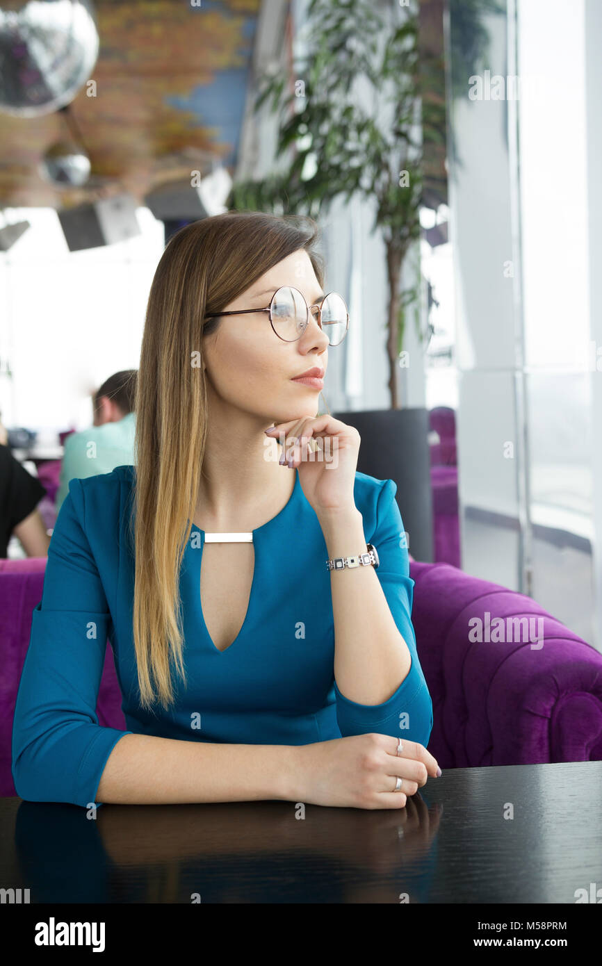 Beautiful girl in glasses sitting in a cafe - Stock Image