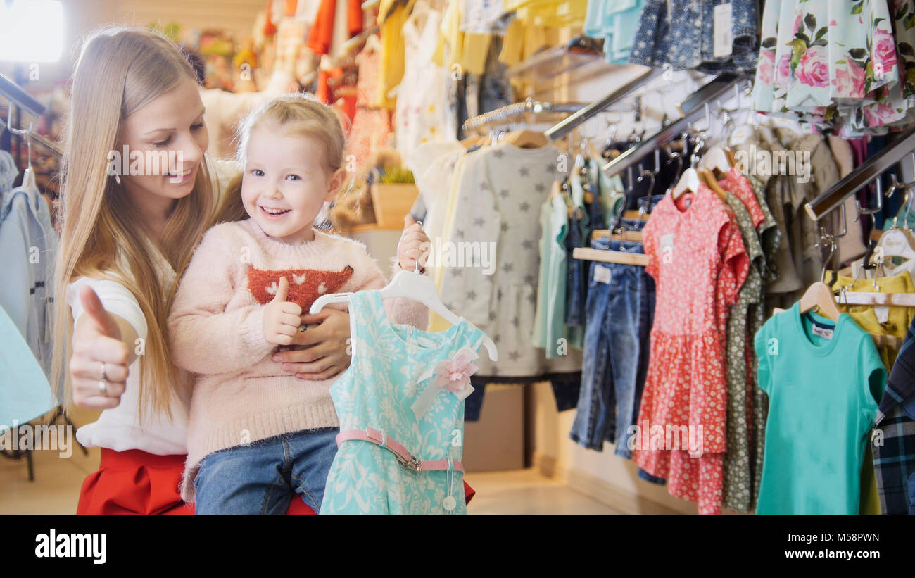 Happy mother with her daughter bought a blue summer dress - Stock Image