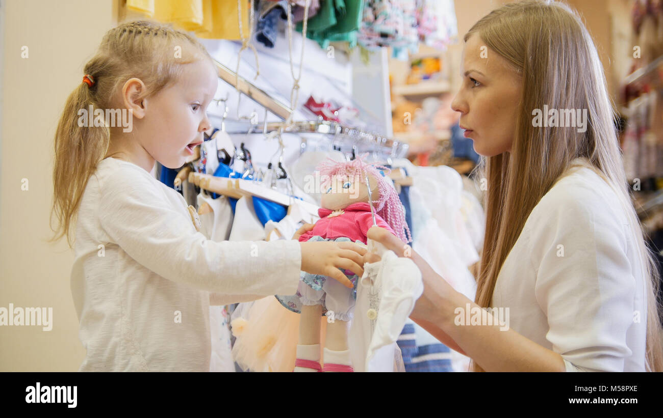 Mom bought the doll to her daughter - Stock Image