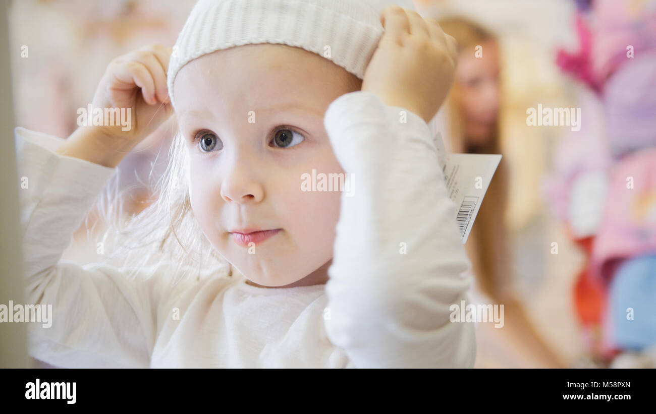 Little girl trying on white caps - Stock Image