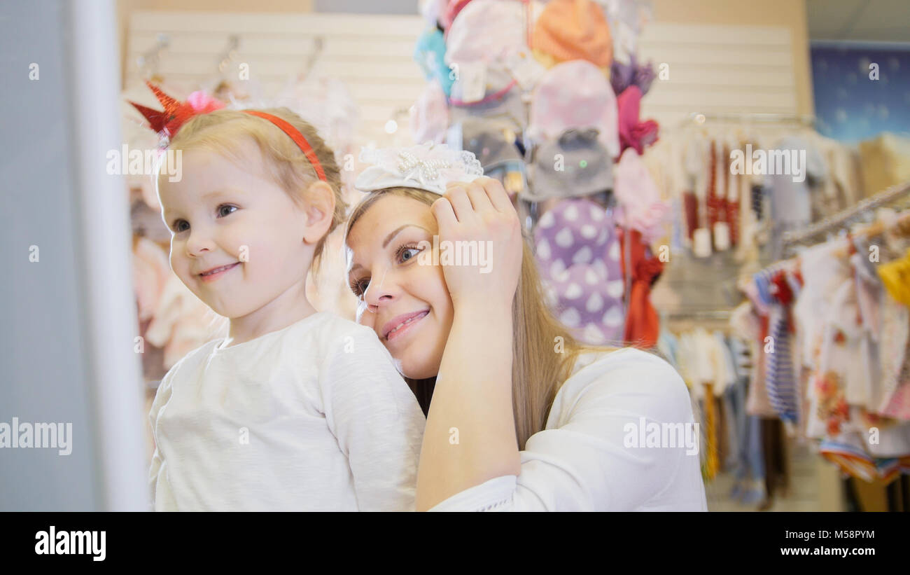 Mother and daughter trying on headbands - Stock Image