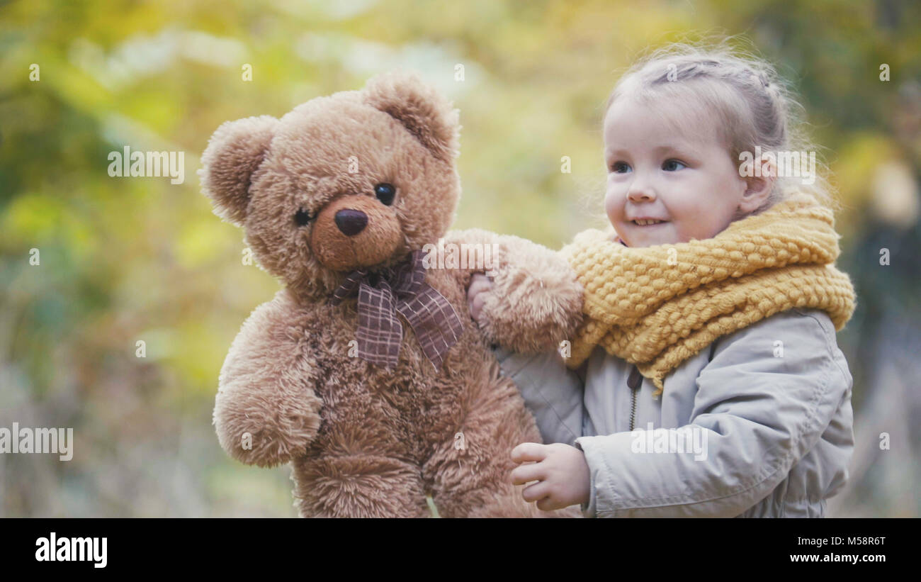 Little blonde girl plays with teddy bear in autumn park Stock Photo