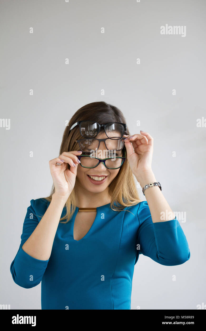 Ophthalmology metaphor - young pretty woman with three glasses on face smiling and looking to camera - Stock Image