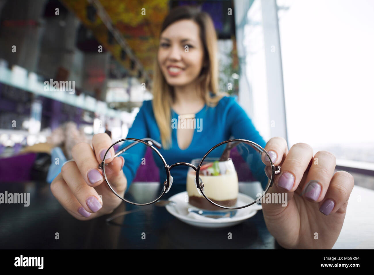 Pretty young girl holding glasses in hands sitting in cafe, ophthalmology - Stock Image