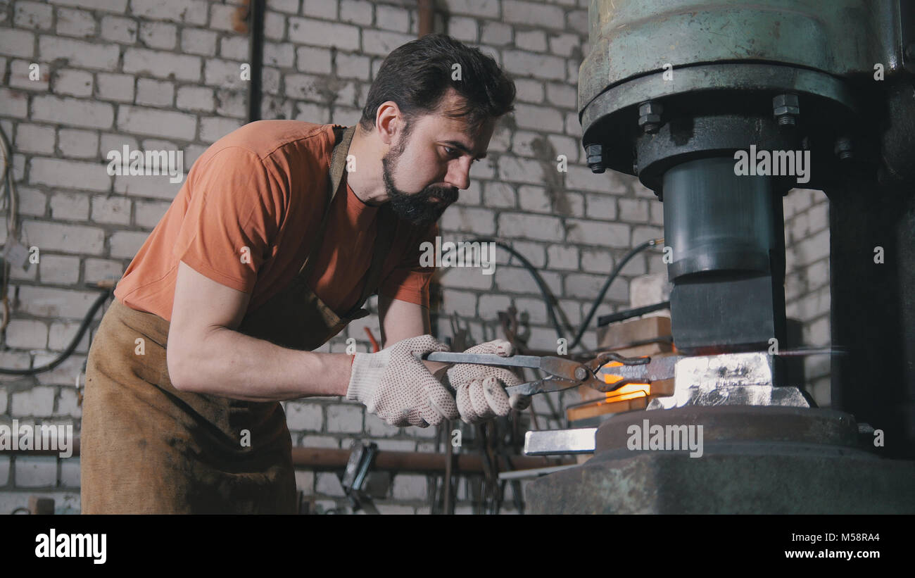 Man blacksmith in workshop forging red hot iron on anvil - small business - Stock Image