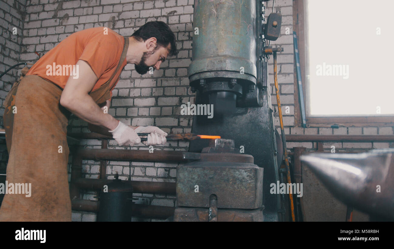 Man blacksmith forges the metal at the mechanical hammer - small business - Stock Image