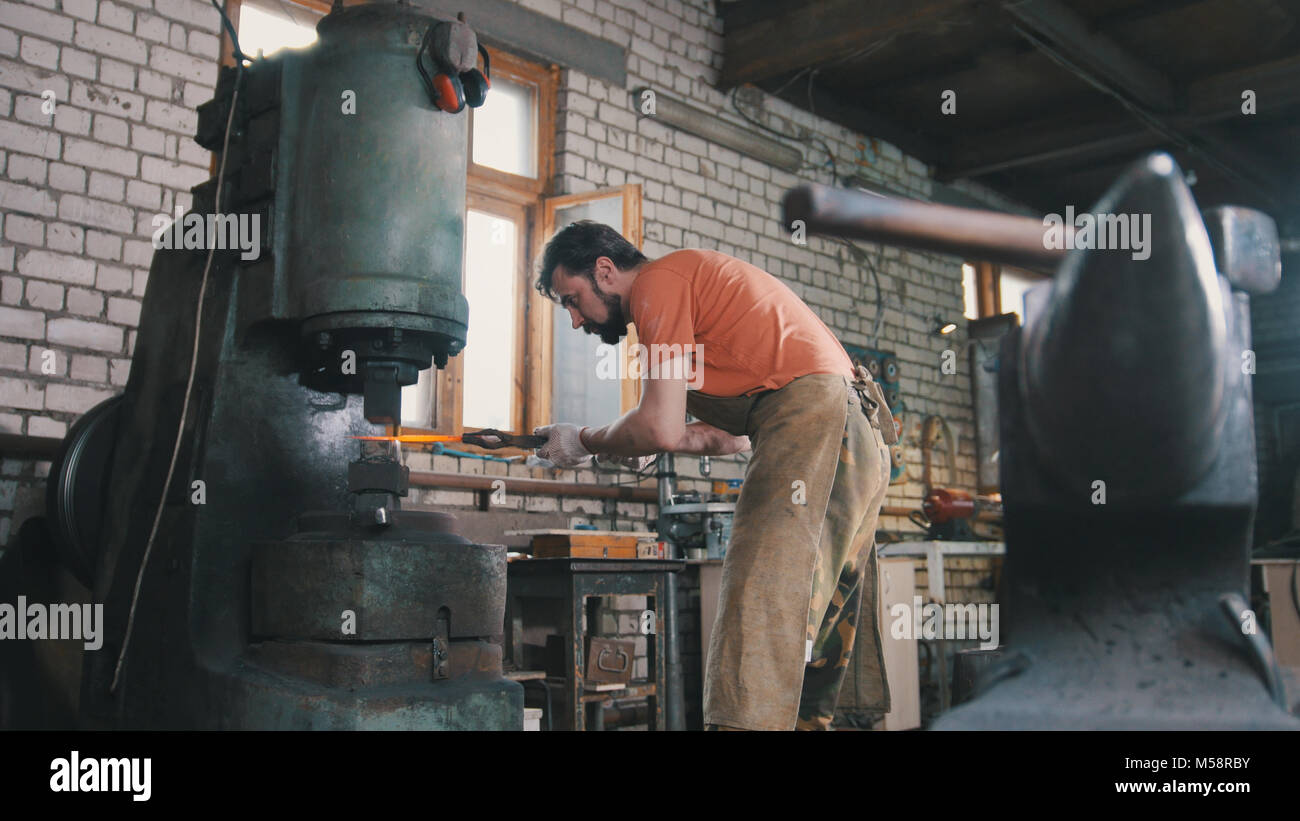 Man blacksmith forges the metal at the mechanical hammer - Stock Image