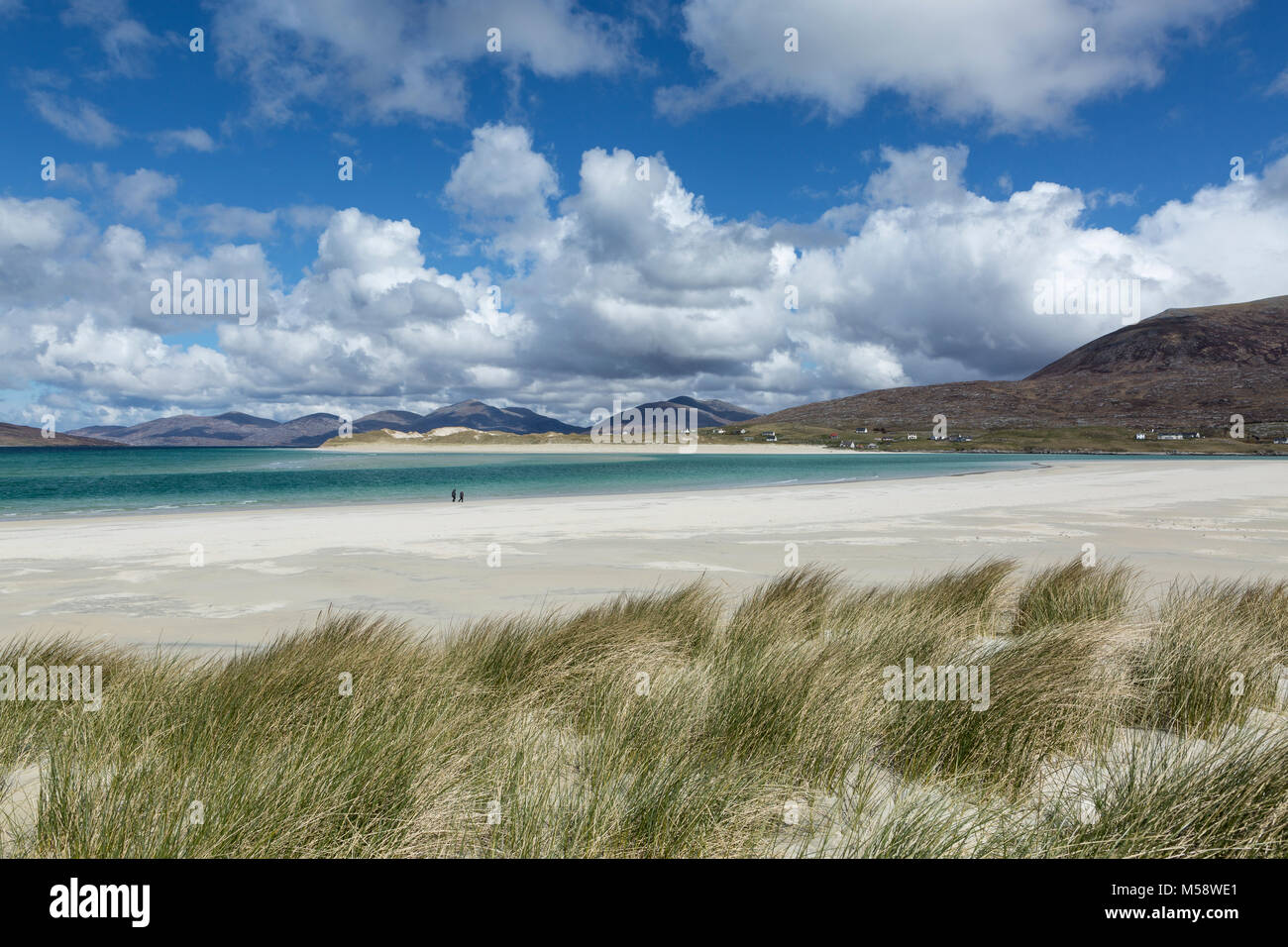 Walkers on the beach at Seilebost, Isle of Harris, Outer Hebrides, Scotland. With the dunes of Luskentyre beach - Stock Image