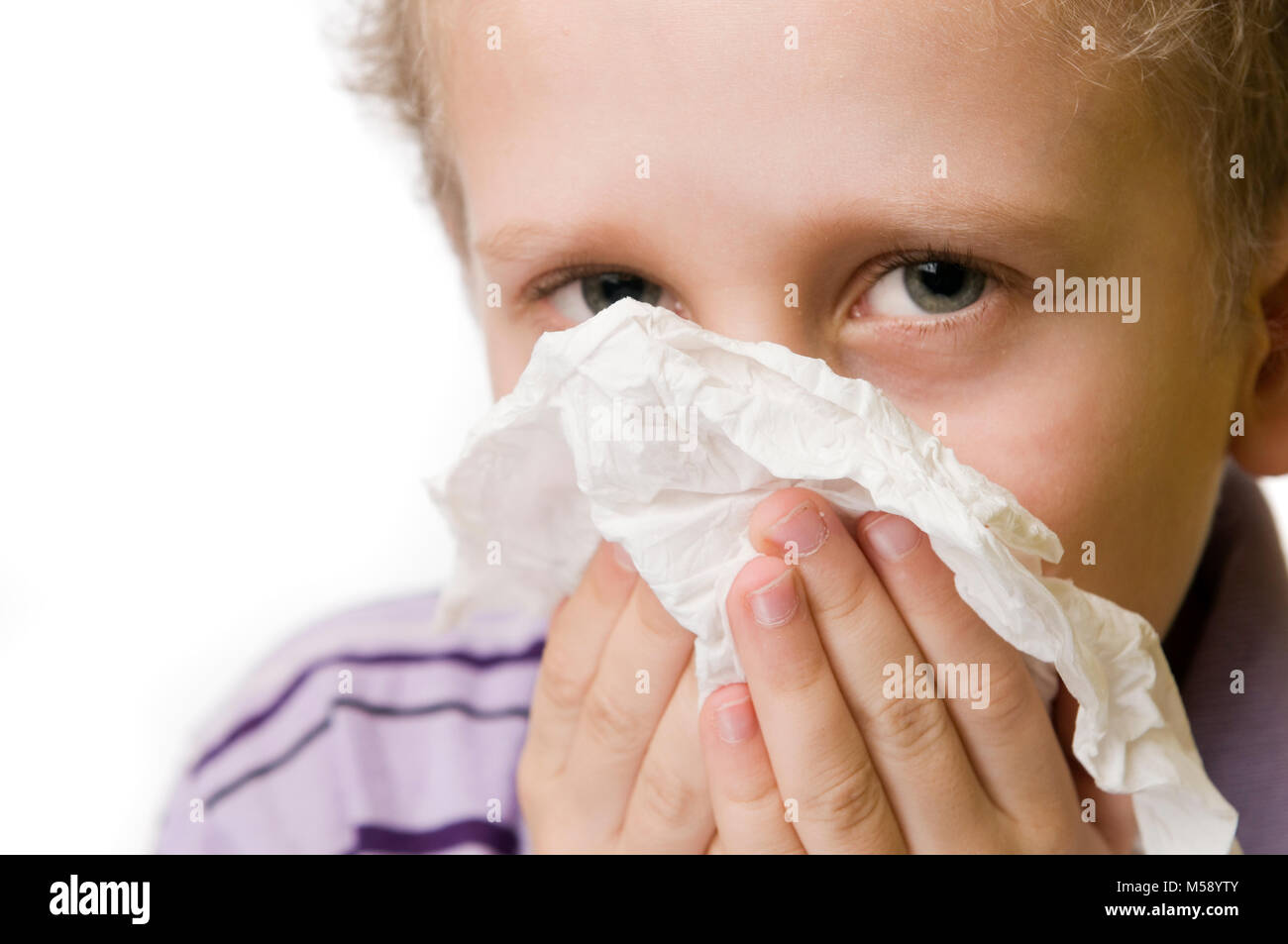 Frontal close-up of a seven-year Caucasian boy up with a tissue paper nose puzend isolated on white. Stock Photo