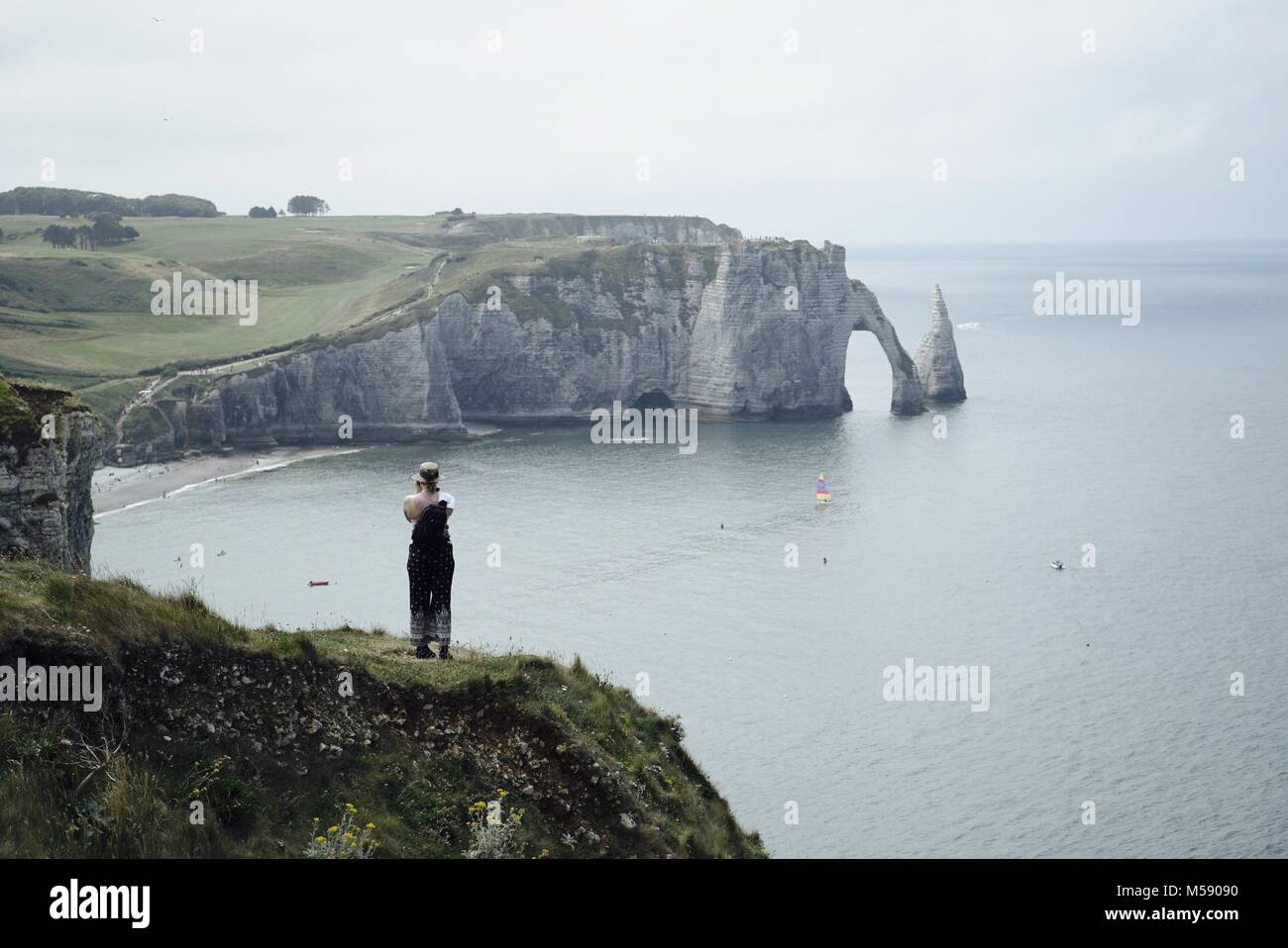 Woman standing on a hill in front of Etretat famous chalk cliff, arch and needle - Stock Image