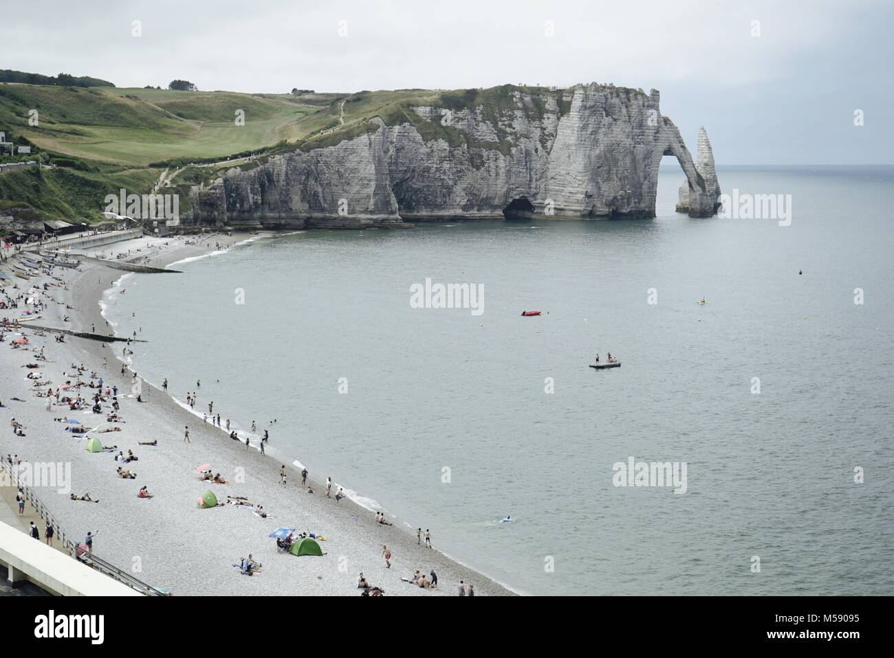 Etretat beach, with its famous chalk cliff, arch and needle in the background - Stock Image