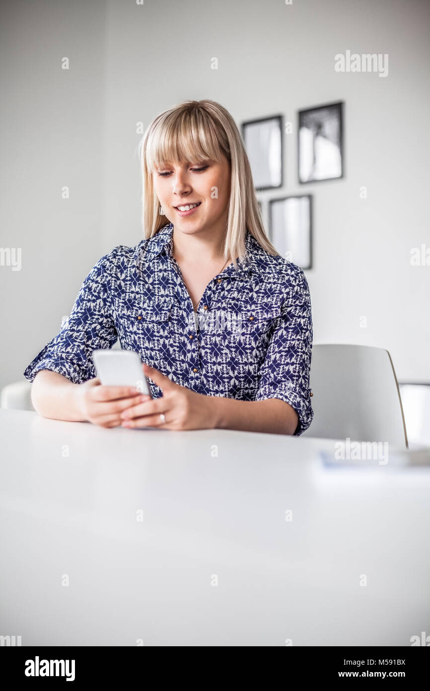 Young businesswoman using smart phone in creative office - Stock Image
