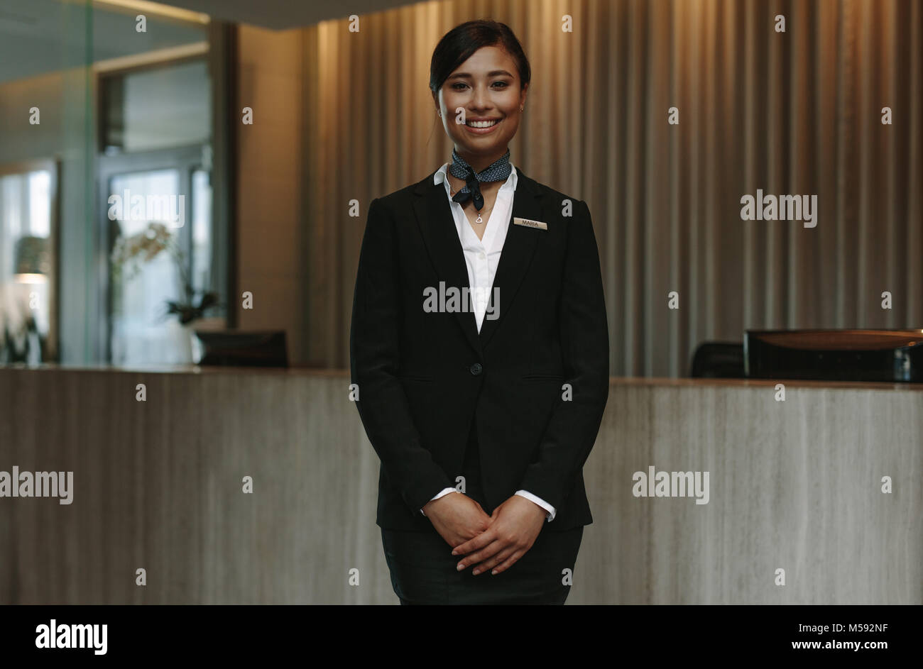 Happy smiling female receptionist in hotel. Beautiful concierge in uniform waiting for welcoming the guests. - Stock Image