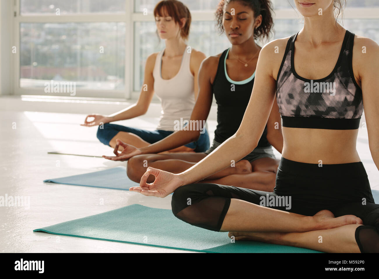 Three women in yoga class sitting on fitness mat with legs crossed and hands on knees. Female meditating in lotus - Stock Image