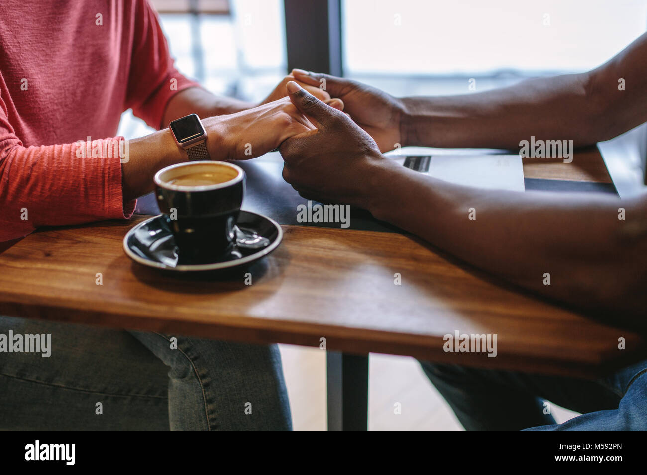 Man and woman sitting at a coffee table holding hands with a cup of coffee on the table. Cropped image of a man - Stock Image