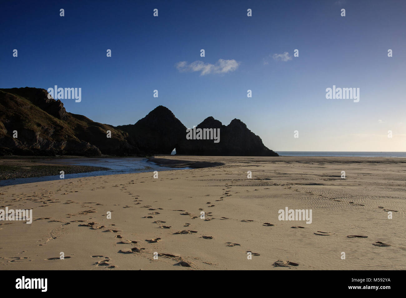 Footsteps on sand Three Cliffs Bay,Gower Peninsula, Swansea - Stock Image