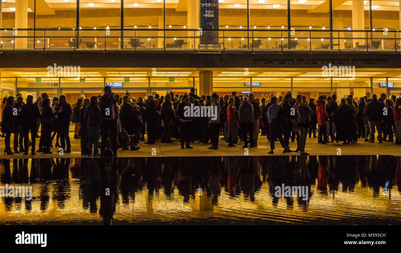 Evening gathering crowd of people before the show outside the concert hall building - Stock Image