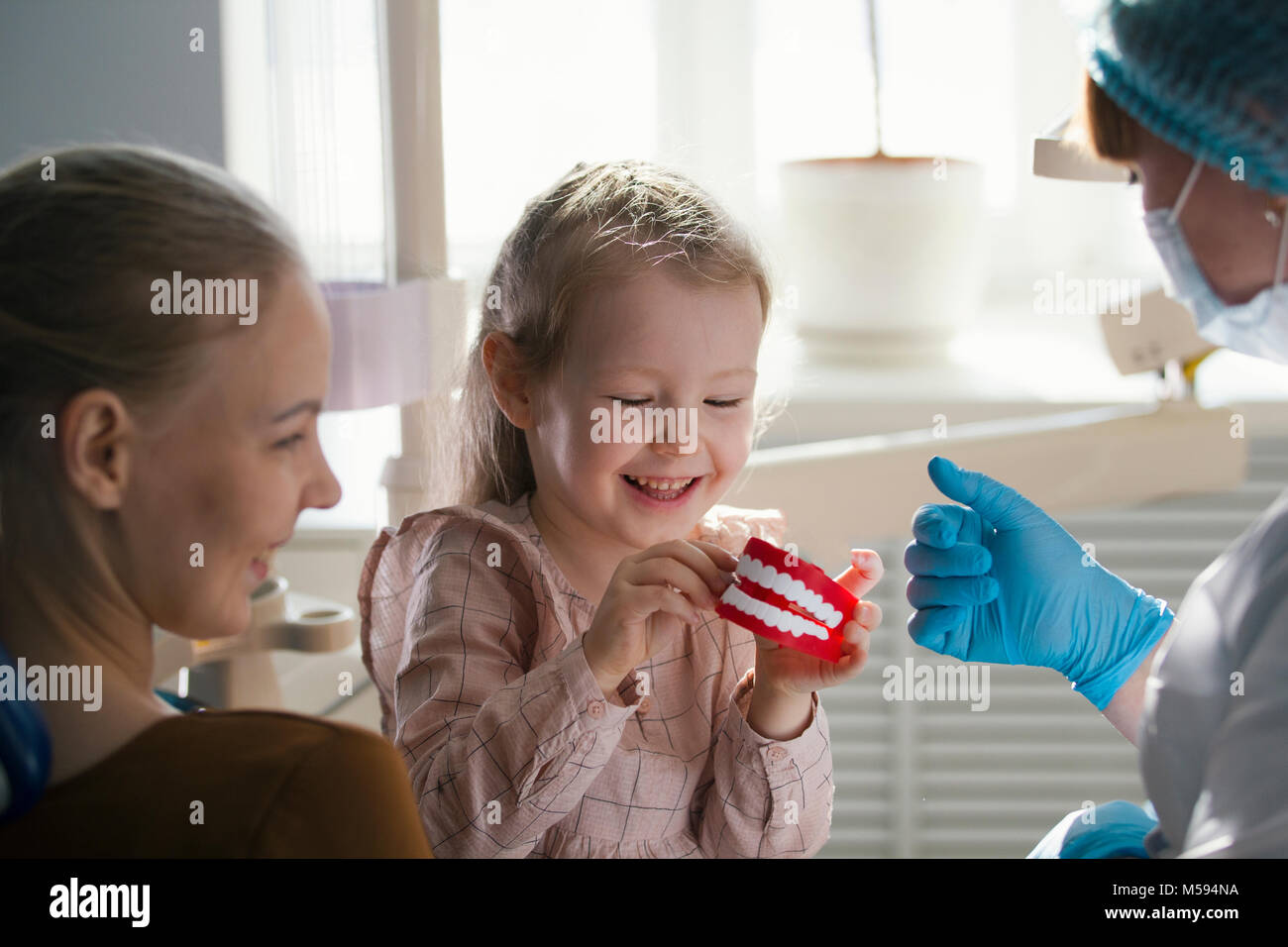 Little girl with mommy in dentist room - conversation with doctor - Stock Image