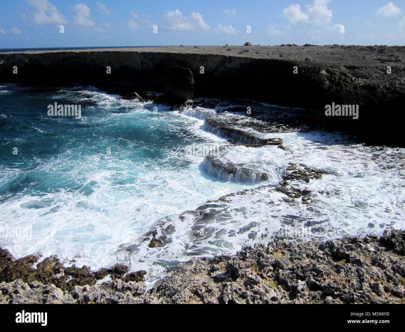 troubled sea at rocky coastline - Stock Image