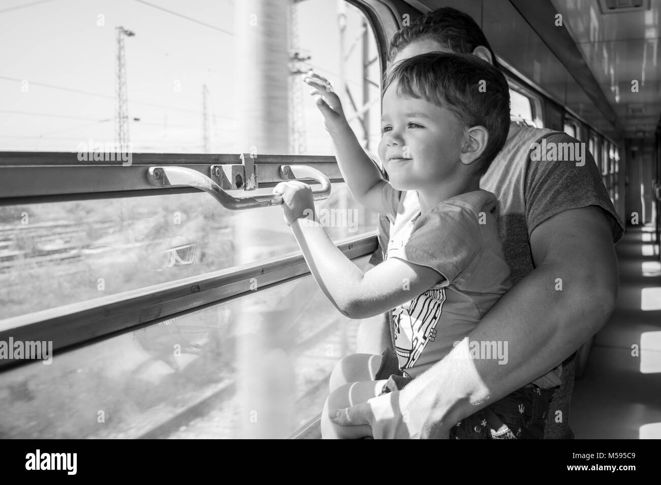 Son and dad travelling by train and waving through the window - Stock Image