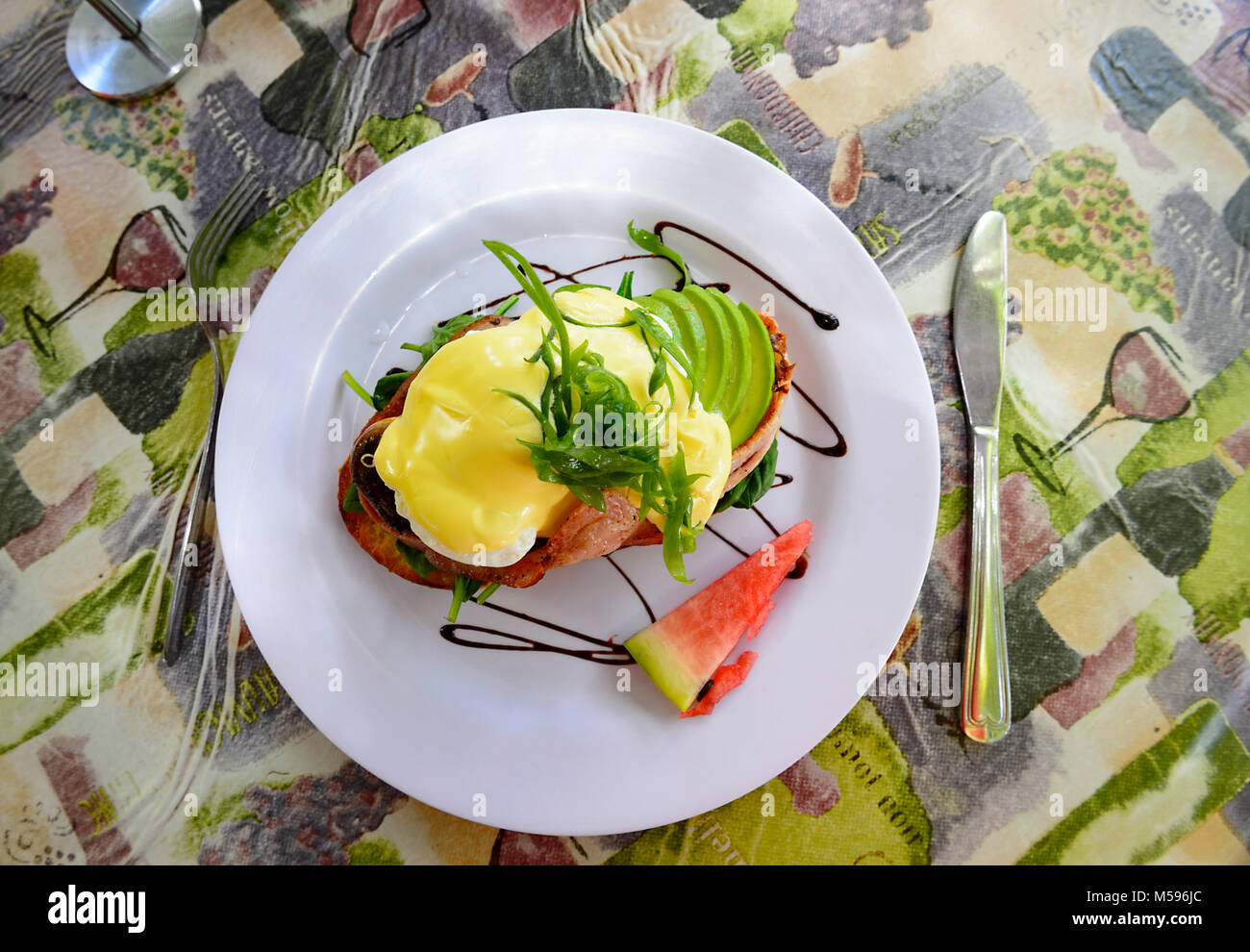 Tasty classic dish of eggs Benedict on a white plate, nicely presented - Stock Image