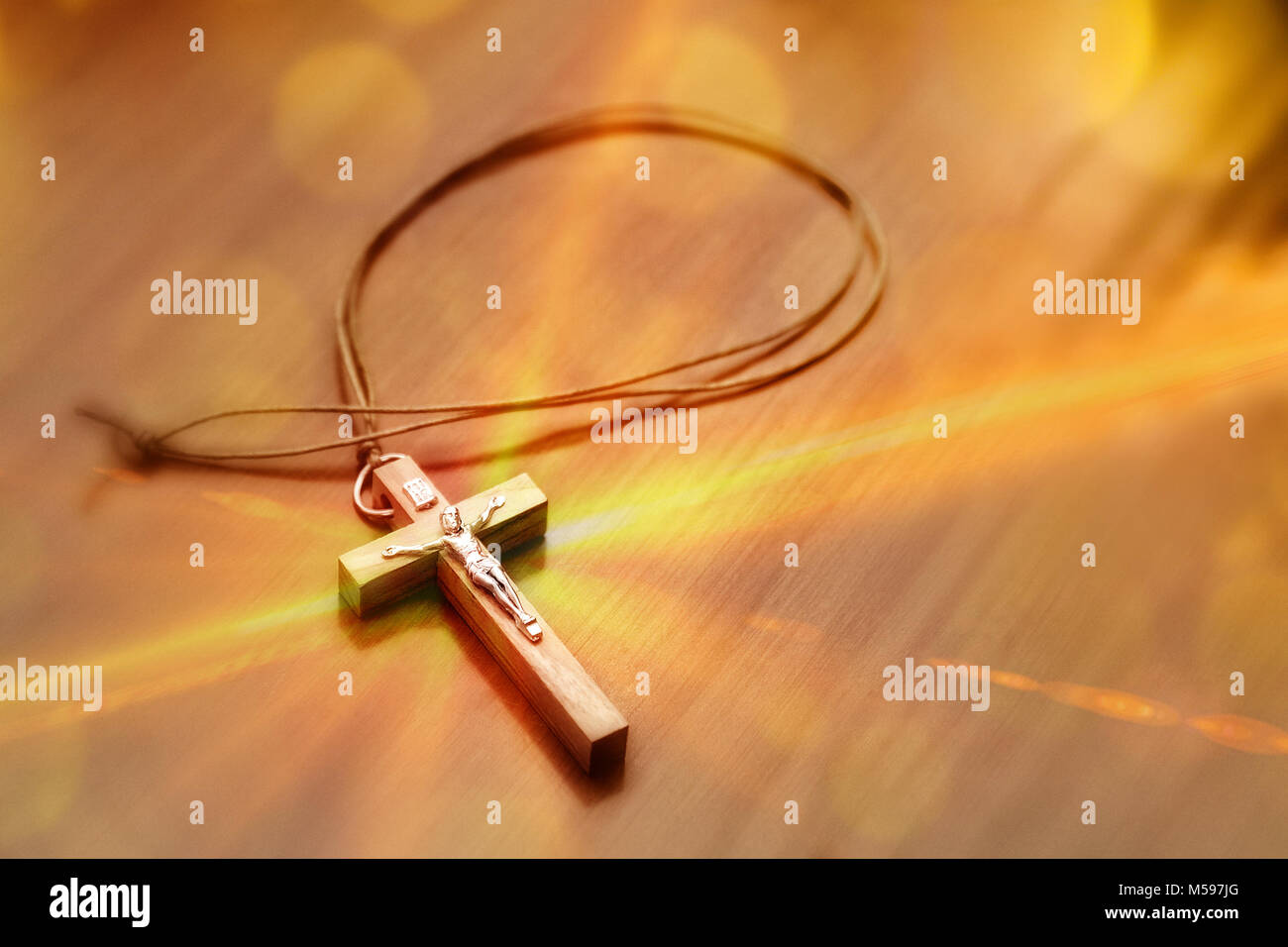 Closeup of crucifix on a wooden table with glitters coming out of it. Elevated view Stock Photo