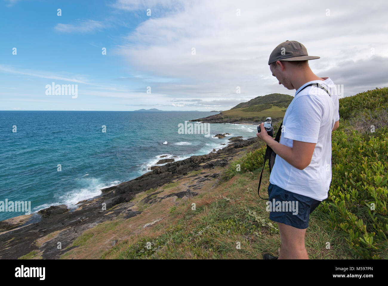 A young man taking photos near the ocean with an analogue SLR camera - Stock Image
