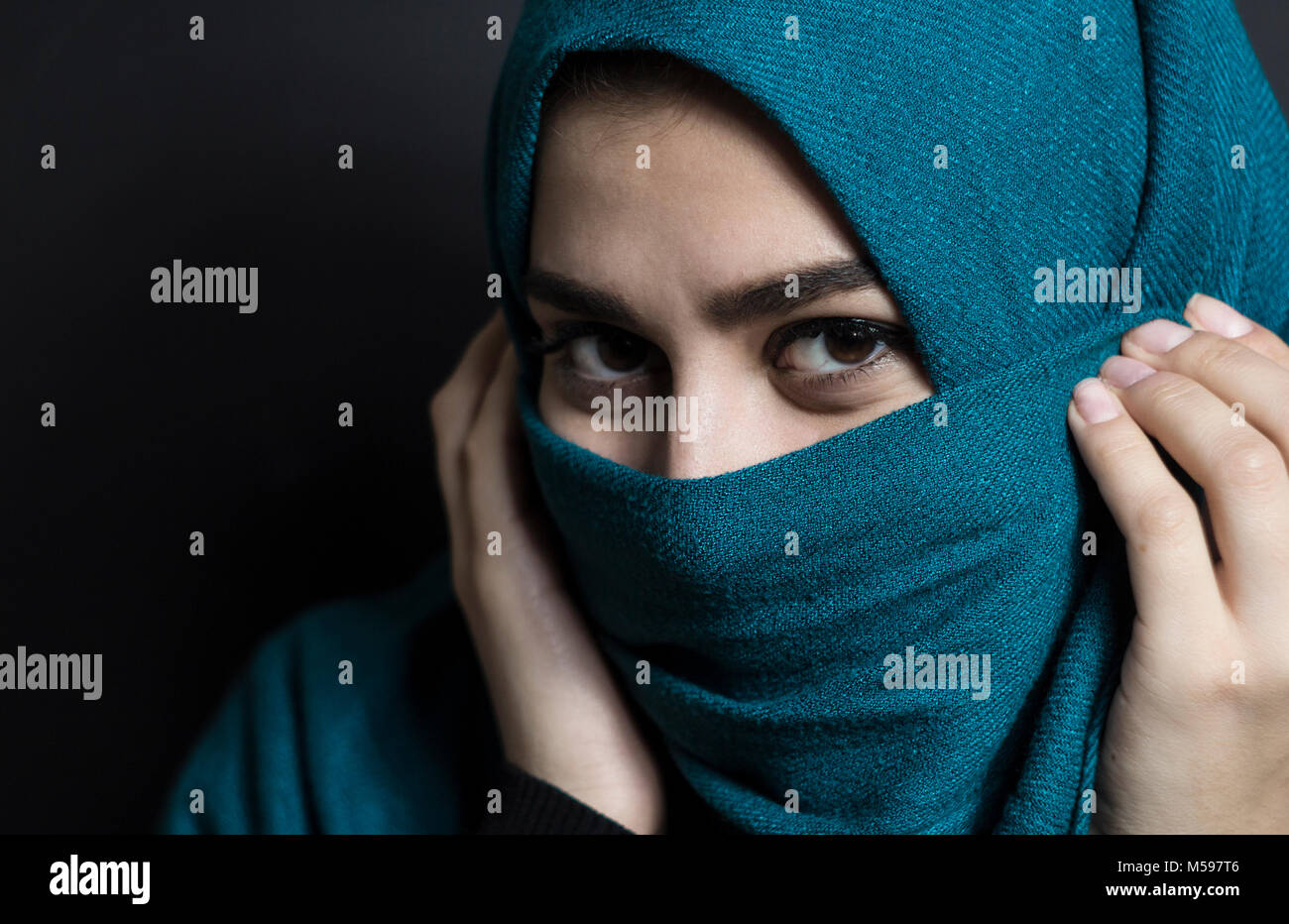 Muslim beautiful girl in hijab. Portrait of an arab young woman on a black  background.