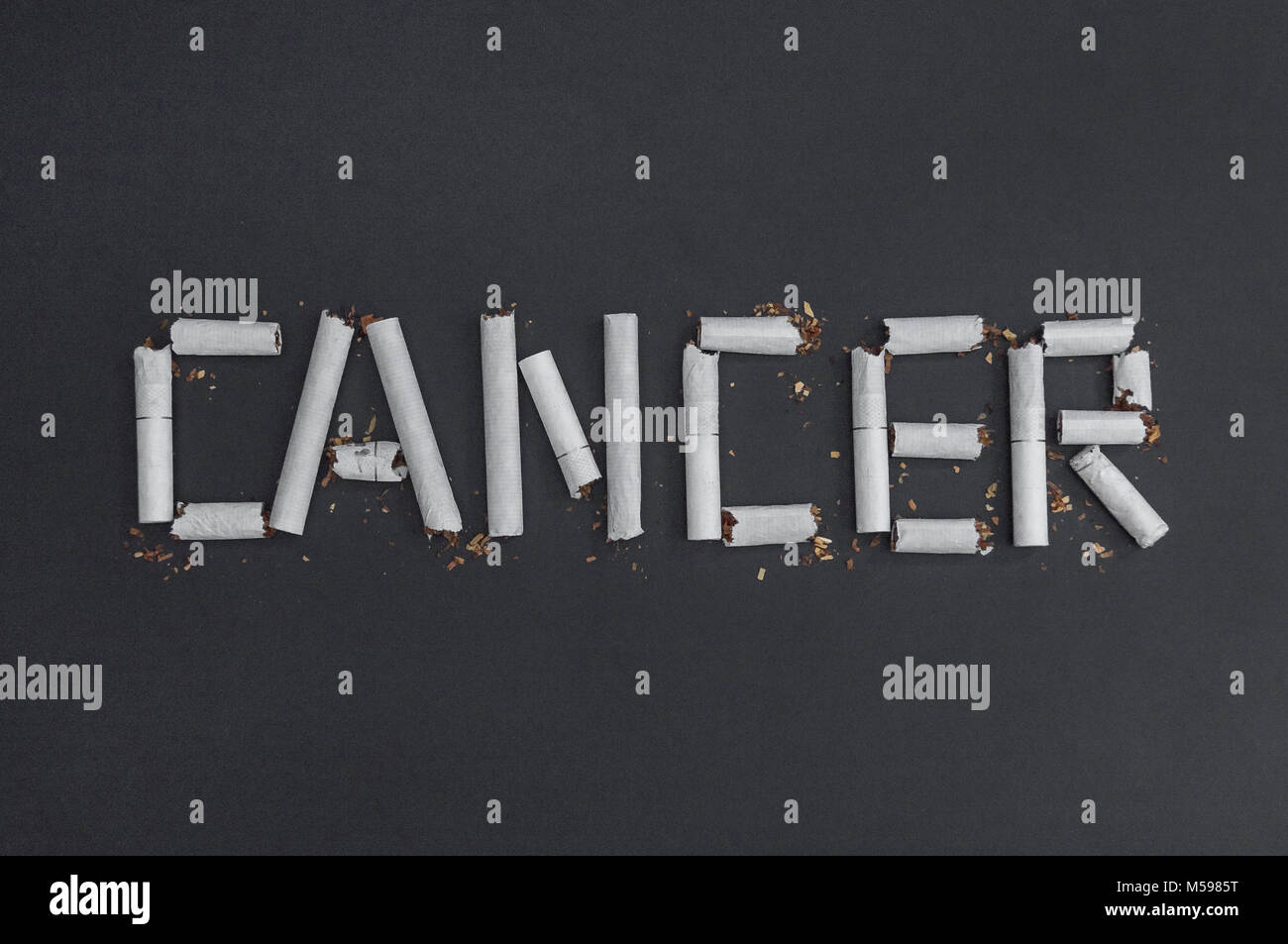 Cancer - an inscription word made from cigarette butts to visualize the harm of smoking. Against smoking - against - Stock Image