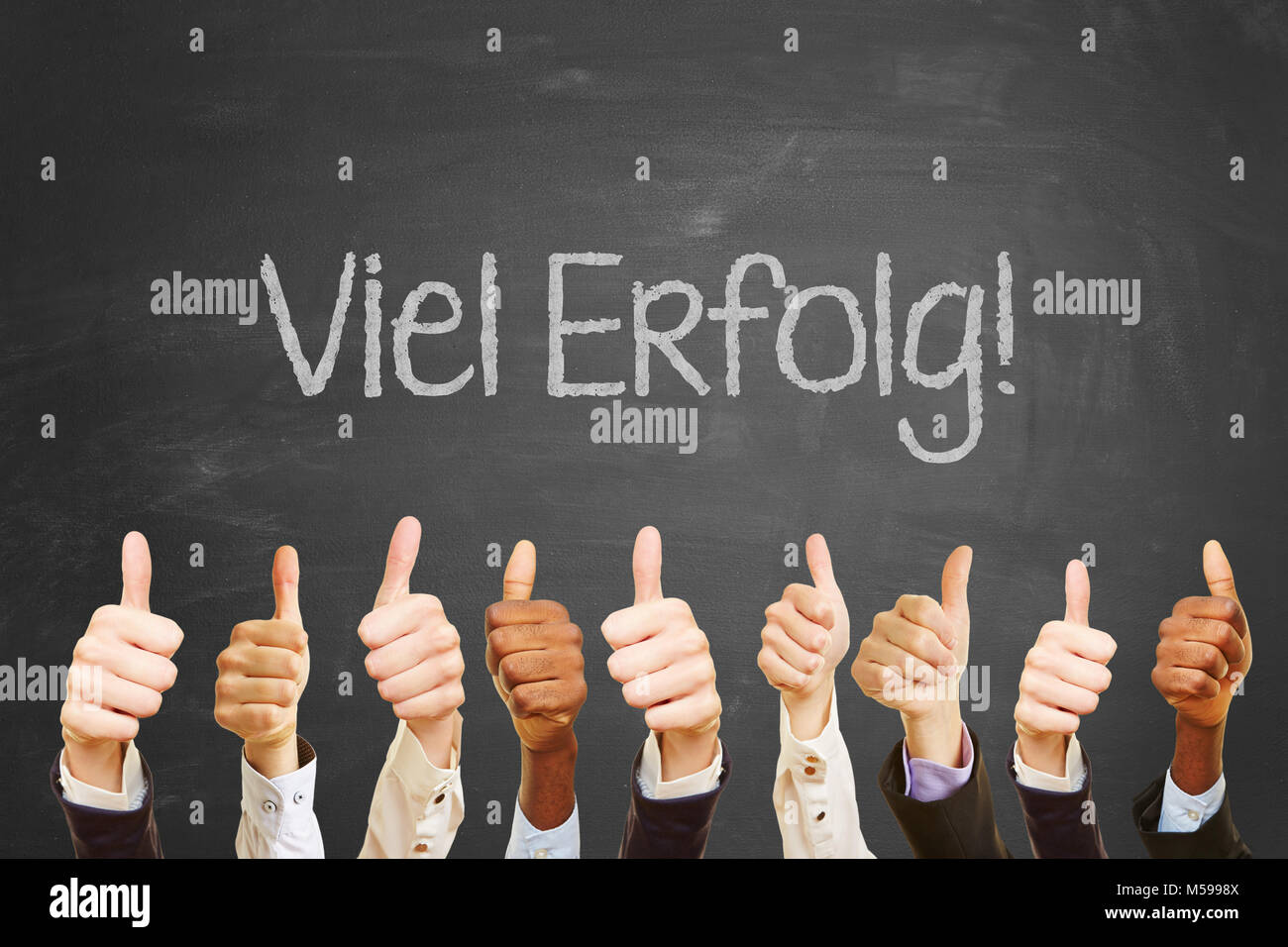 German text 'Viel Glueck' (Goog luck!) on a blackboard with thumbs up - Stock Image