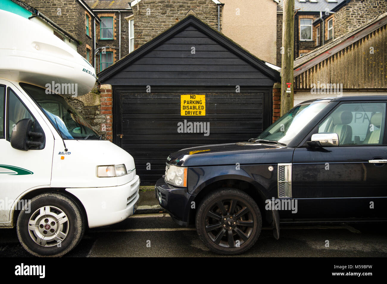 Inconsiderate motorists UK: Two parked vehicles blocking the entrance to  a private garage despite there being a - Stock Image