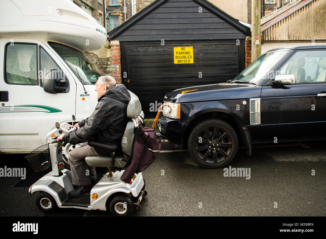 Inconsiderate motorists UK: A man riding on a disability scooter passing two parked vehicles blocking the entrance - Stock Image