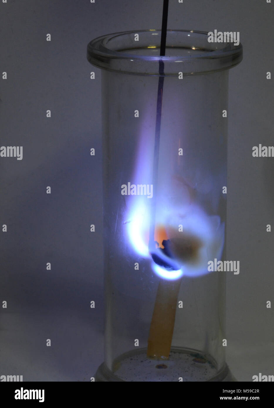 Sulphur burning in a glass with oxygencausing yellowish-brown smoke, a vet strip of indicator paper takes an orange - Stock Image