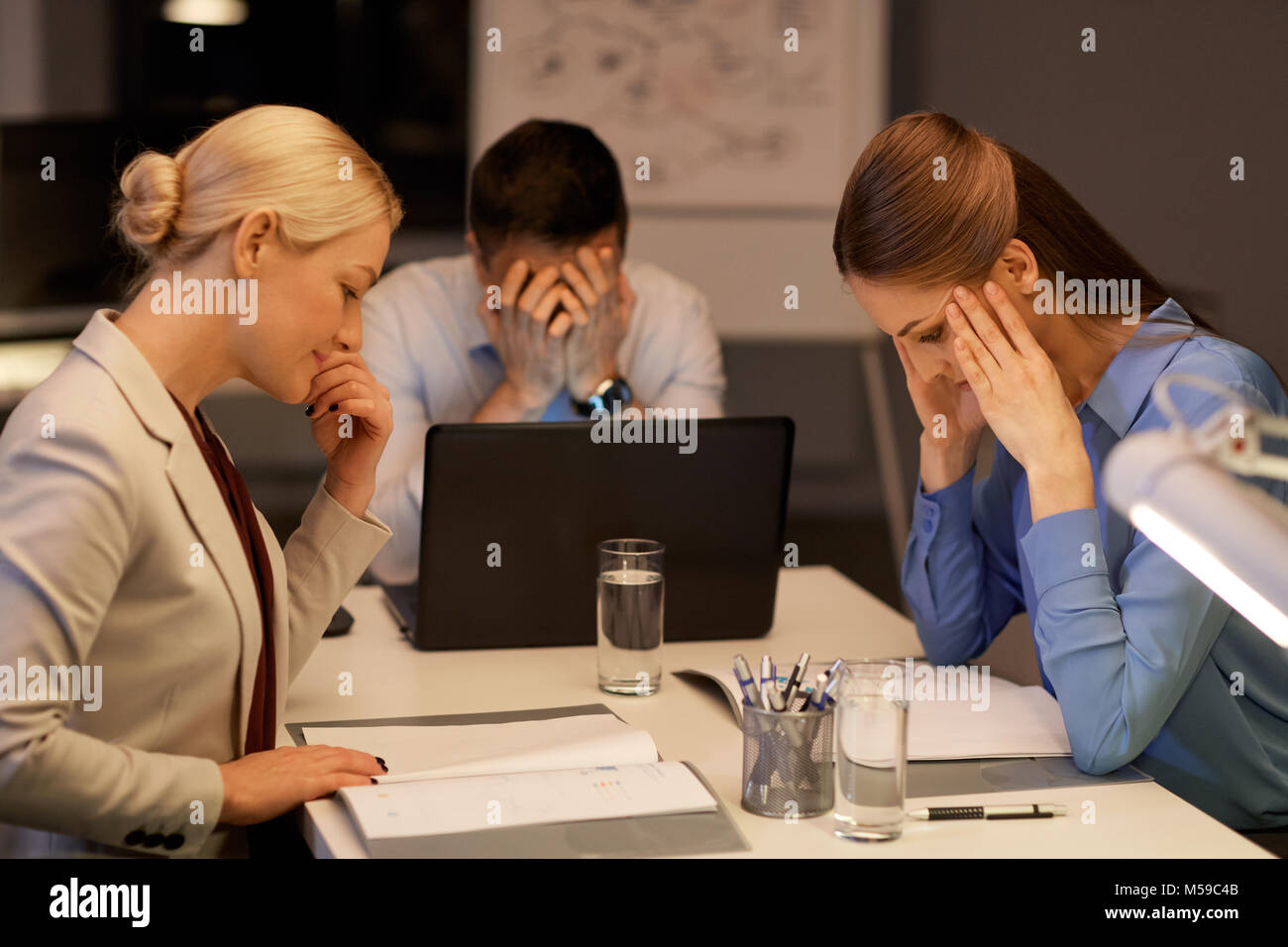 business team with laptop working late at office - Stock Image