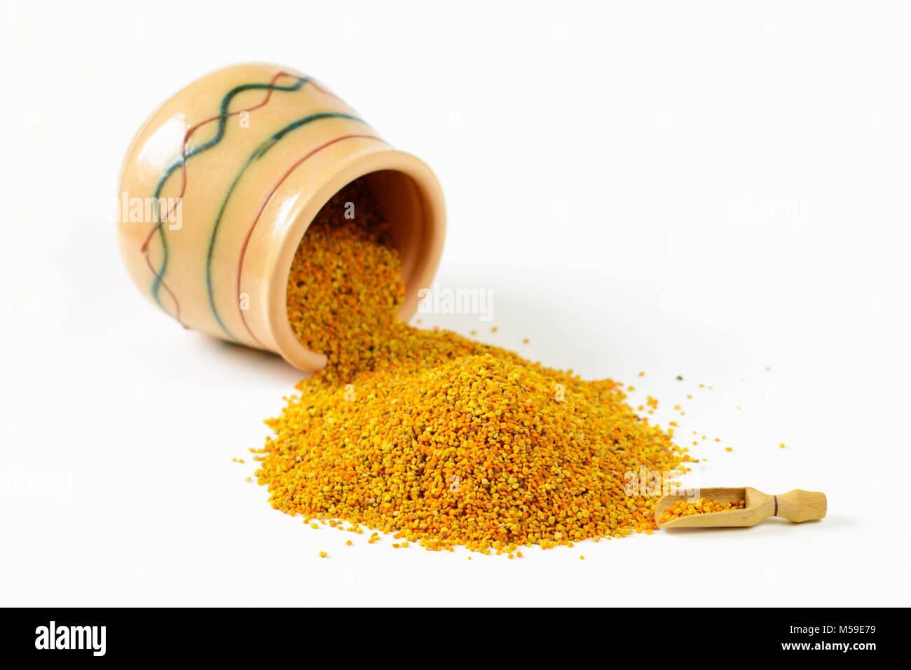 Heap of bee pollen granules, a wooden scoop and an overturned glazed clay pot full of pollen. Selective focus. Closeup. Stock Photo